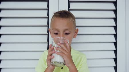 cálcio : Portrait of a healthy kid boy with a glass of milk. A boy is drinking milk in about white door. Healthy eating. The right way of life. Little boy drinking milk