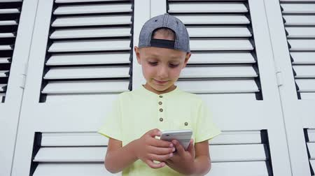 pré escolar : Portrait of a satisfied cute little kid playing games on smartphone isolated over white background. Child playing online games on smartphone highly concentrated