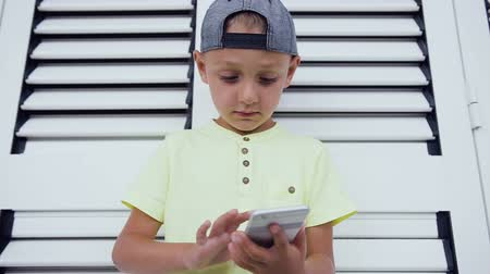 boyish : Young teenager in cap playing game on smartphone, isolated on white door background. Child playing with smartphone technology. Close-up of young boy who write message on his smartphone Stock Footage