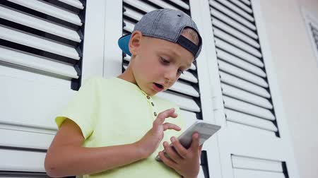 андроид : Close up of face and hands of 5-6 years old boy playing computer games standing near white window in outdoor. Kid using telephone. Concept of teen and technology