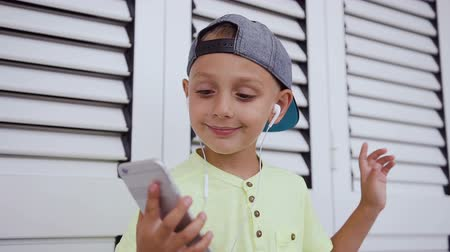 čepice : Beautiful little kid in t-shirt and cap who listens to music in headphones from the grey smartphone and dancing in the white background in indoors. Attractive baby boy dance while listening to music from the phone Dostupné videozáznamy