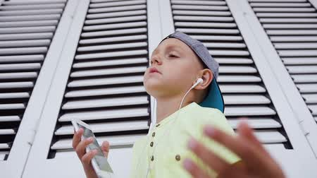enjoys : A little boy in cap and t-shirt listens to music with headphones from smartphone on the white background. He closes her eyes and plunges into the world of music dancing at a rhythm