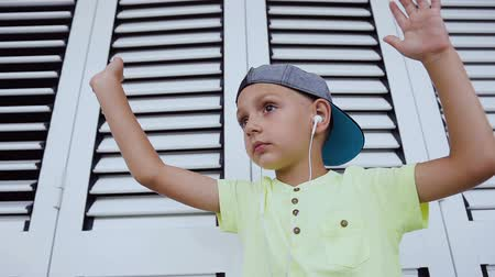 wearing earphones : Caucasian little boy is listening to music and dancing gesturing with his hands. Portrait of a funny boy who dancing listen to good music in earphones from smartphone