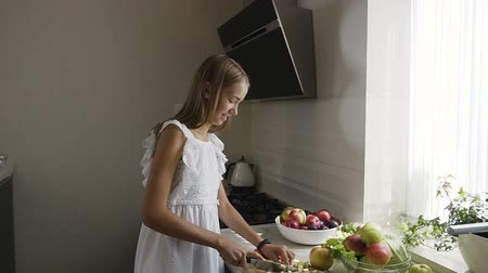 biber : Attractive teenage girl in white dress is preparing fruits salad in the kitchen. Healthy conscious girl is cutting fruits for a vegetarian meal at home in the kitchen