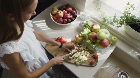 biber : Top view. Attractive blonde girl in white dress is preparing fruits salad in the kitchen. The girl slices a apples in her kitchen at home. Healthy eating Stok Video