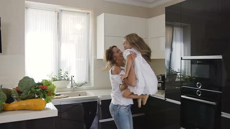raises : Mother with daughter fun spinning around herself at home in the kitchen. Beautiful woman in a light clothing raises her charming baby girl and starts joyfully spins around herself and smiles. Happy young woman playing with daughter at home in the kitchen