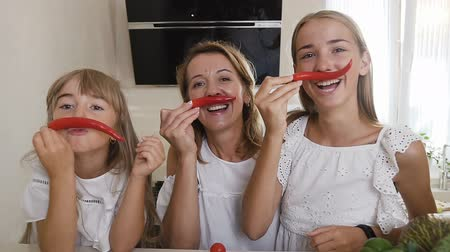 chili : Two sisters and their mother dressed in white clothes are having fun with chili pepper at home in the kitchen. Girls make mustache from red pepper chili and have fun looking at the camera Stock mozgókép