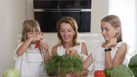 akut : Young woman and two girls dressed in white clothes are playing with chili pepper and green dill at home in the kitchen. Portrait of a mother and daughters with a vegetable chili pepper in indoors Stok Video