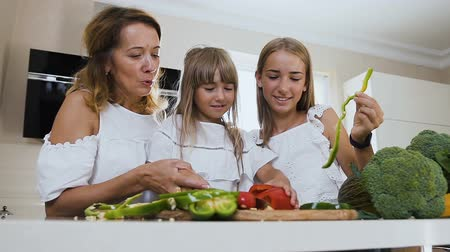 biber : Beautiful mother teaches her younger daughter to cut a pepper with a knife and the older sister eats these vegetable at home in the kitchen. Little girl cooking together with loving mom and sister at home in modern kitchen