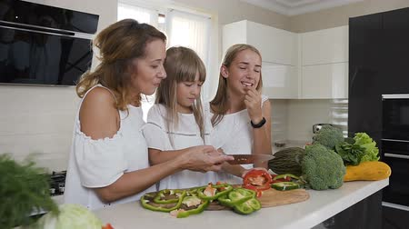 biber : Happy mother and two her daughters is cooking vegetables for dinner at home kitchen. Food, healthy eating, family Stok Video