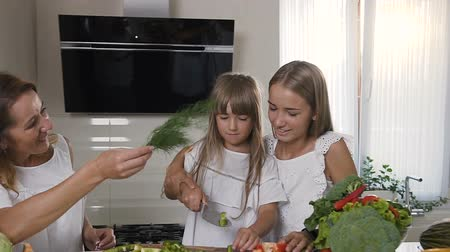 prepairing : Two sisters with their mother in white dresses is cooking healthy vegetable salad together at home in the kitchen. Two girls are preparing a vegetarian salad
