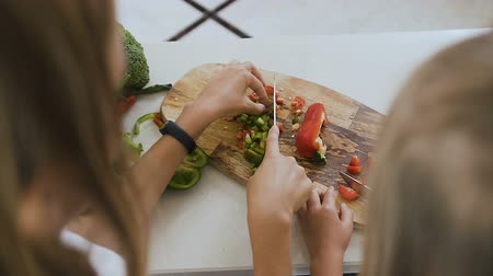 biber : Close-up shot hands of the teens girls using kitchen knife learning to cut the green pepper vegetable preparing a food at home in the kitchen. Two sisters learn cut vegetables with a knife Stok Video