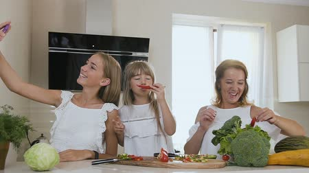 razem : Attractive smiling woman with two daughters do making selfies, photos on smartphone in the kitchen at home. The girls are photographed with vegetables on the smartphone in the home kitchen