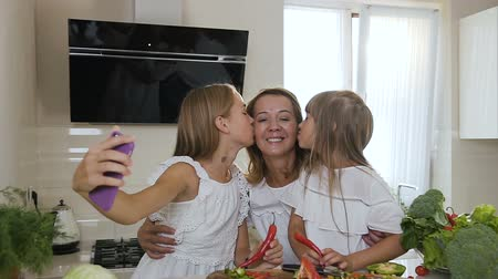 photograph : Portrait of a two cute sisters who kiss their beloved and attractive mother in the while cooking eating at home in the kitchen. Girls dressed in white clothes kissing mother and doing selfie photo on smartphone at home kitchen