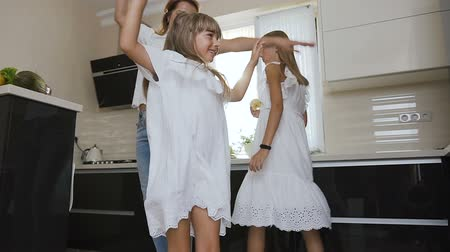 kočkovitý : Happy little girl with her sister and mom in white clothes are dancing and listen music while cooking eating in kitchen at home. Happy family Dostupné videozáznamy