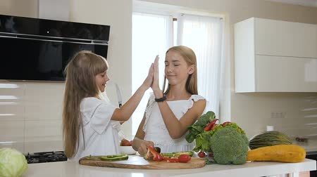biber : Two sisters with long hair in white dress are cutting fresh vegetables on a wooden bench in a modern kitchen. Attractive girls are cutting green and red pepper paprika and giving each other five after cutting of vegetable