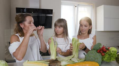 ingrediente : Close-up a young caucasian woman with two her daughters in white clothes are cleaning, shucking, and preparing to cook fresh corn in the kitchen at home