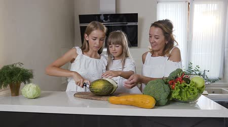 мускусная дыня : Mom and two her daughters cook in the kitchen: woman teaches her daughters to cut green melon. Cute family from mom and two girls prepare vegetarian salad at home in the kitchen