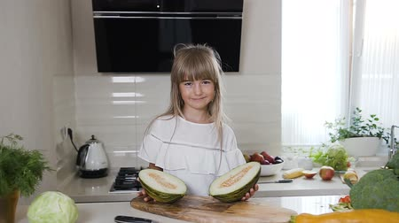 мускусная дыня : The cute little girl in white dress on a wooden board holds a green melon cut in half in the home kitchen. Healthy food, vegetable, child