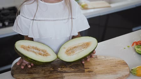 мускусная дыня : The girl in white dress holds in her hands a melon cut in half in the home kitchen. Close-up cut of split green melon in half on a wooden board in the hands of a little girl Стоковые видеозаписи