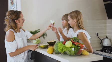 мускусная дыня : Mother and daughters cutting and eat green melon on the kitchen work surface at home. Woman is cutting a melon and then eat it with her daughters Стоковые видеозаписи
