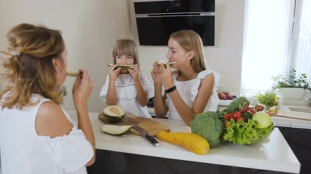 melão : Two cute teens sisters and an their mom in white clothes eat ripe melon at the kitchen table at home. Healthy food, diet, vegan