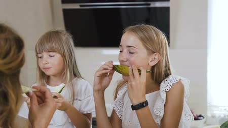 melão : Close-up. Cute caucasian children in white clothes eating fresh melon. Attractive family eatting melon at kitchen table at home