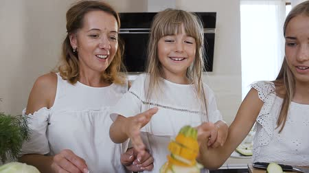 cuketa : Cute little girl with her mom and older sister dressed in white clothes having fun makes a pyramid with zucchini at the kitchen table at home in the kitchen. Happy family, healthy food, vegetables