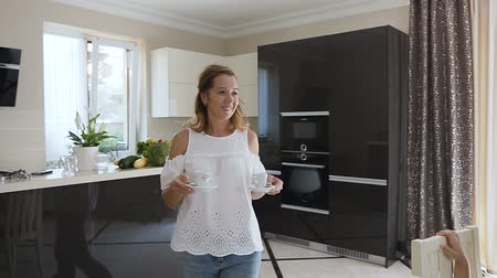 americano : An attractive wife serves her husband a coffee in the morning at kitchen room. Americano. Coffee time. A beautiful woman with her husband are drinking coffee in the morning