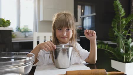 tvaroh : Small funny girl is cooking and mixing flour in the bowl. Portrait shot. Close-up little girl mixing flour with spoon while cooking dough in the kitchen at home