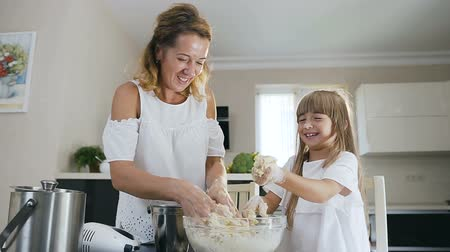 taneli : Attractive good looking mother and her small daughter trying to clean their hands from a dough while cooking together in the modern kitchen at home. Cheerful family bake cookies Stok Video