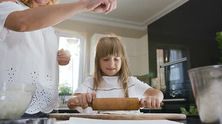 turta : Good looking mother teaching her young little daughter to cook and kneading a dough for cookies on the table in the kitchen at home. Young woman and small girl preparing pasta or pizza together using a rolling pin on a sheet of kneading dough