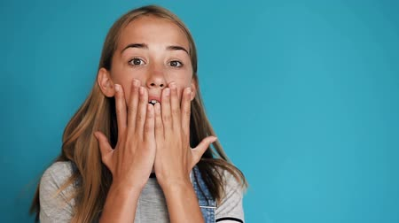 потрясенный : Beautiful happy surprised girl with positive emotions over blue background. Portrait of cute surprised and shocked teen girl. Happy, shocked, surprised and smiling woman standing isolated over blue background while looking camera