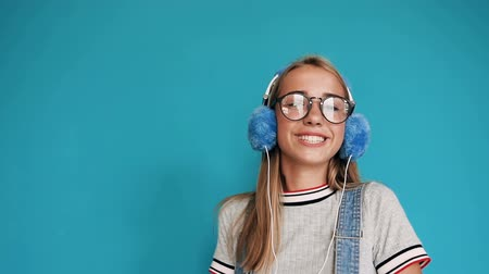 śpiew : Cute teenage girl dancing and moving to the rhythm listening music in headphones in indoors at blue background. Girl in glasses smiling and listening to music in headphones. Portrait of a beautiful relaxing girl