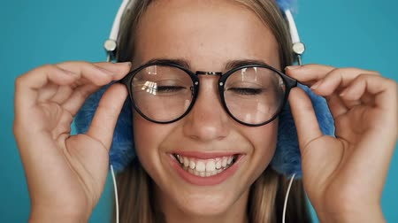 model : Portrait of the beautiful teen girl in glasses and with headphones looking straight in the camera and smiling cheerfully on the blue or turquoise wall background. Close up. Indoors