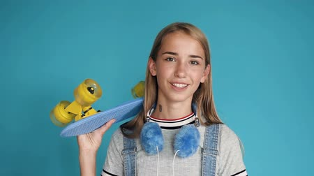 deskorolka : Portrait of a teen girl with skateboard on her shoulder on blue background. Free time of teenagers. Leisure and sport activity. Happy pretty teenage girl holding skateboard on her shoulders and looking at camera while standing against blue wall