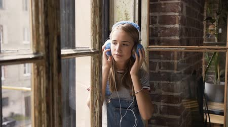 oturur : Portrait of young attractive girl on window background listening to music with headphones. Leisure and relaxation at indoors.Teen girl enjoying the tunes in her headphones