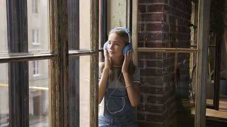 poblíž : Portrait of young attractive girl on window background listening to music with headphones. A beautiful girl sits near a window with headphones listening to music from smartphone