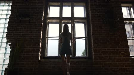kabarık : Rear view of european young girl opening a window into the street in summer morning day. Slim girl is walking over hall and approaching to big windows. Attractive young teen girl is looking in a window