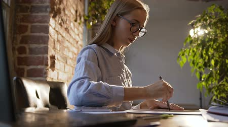 szabály : Beautiful student girl in glasses sitting by the table uses the pen and ruler on a sheet of paper. Business woman making a report on successful marketing. Vision of contemporary workspace