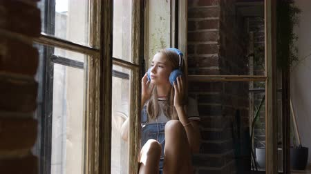 wearing earphones : Portrait of young attractive girl on window background is listening to music with headphones. A beautiful teen girl sits near a window with headphones listening to music from smartphone Stock Footage