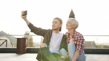 pattinatrice : Handsome stylish couple are sitting on longboard skateboard on the rooftop playground of industrial building and making selfie photo on the smartphone. Young guy and girl having fun are doing the selfie photo on the smartphone at sunset