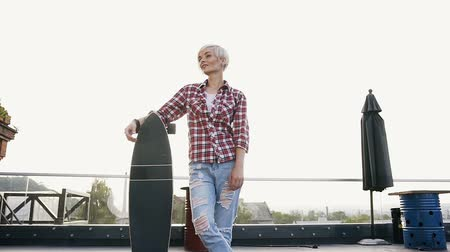 トレンディー : Beautiful hipster blonde girl hold longboard on the roof in the modern building in sunny weather. Portrait young woman in red checkered shirt and jeans is standing on urban street with longboard at su