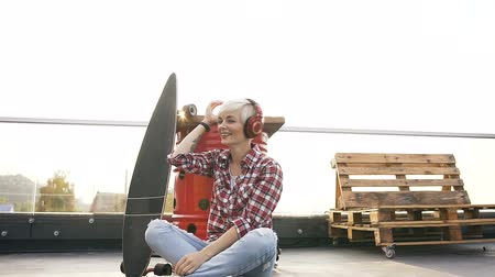 tetőtéri : Beautiful smiling hipster girl listening to music with headphones. Young smiling blonde girl listening music in headphones, dances while sitting on the floor near the skateboard at outdoors Stock mozgókép