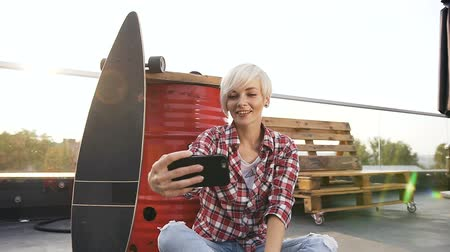 oturur : Happy blonde girl doing selfie photo with smartphone outdoors on the modern building roof. Cheerful attractive female dressed in checkered shirt making selfie on smartphone camera, posing, sits on the fllor on street Stok Video