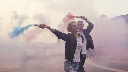 granada : Happy couple running with colored smoke on the terrace roof of the modern building. Young hipster couple with colored smoke bombs at sunset. Outdoors Vídeos