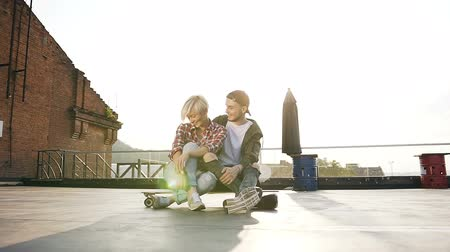 oturur : Friends are having fun while sitting on a skateboard on the outdoors. Young hipster couple having fun with long skateboard on the rooftop of an modern building Stok Video