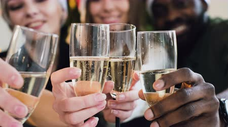 kabarcıklı : close-up the hands of people of different races who hold wine glasses of sparkling wine. bubbles in wine glasses with white wine against the background of beautiful guys and girls. The concept of christmas, new year and celebration.