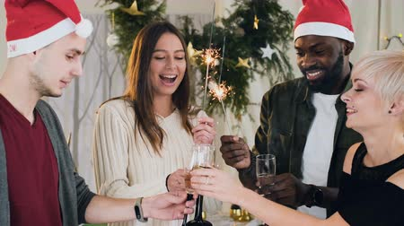 x mas : the company of wonderful people of different races of wine glasses with white sparkling wine against the background of Christmas lights and decor