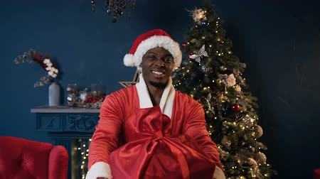 ded : Happy african man in santa claus costume holding the gift on the Christmas tree background.